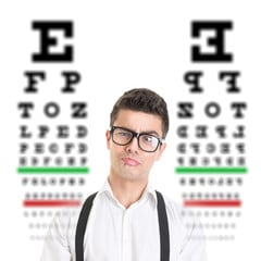 man wearing glasses standing in front of eye charts