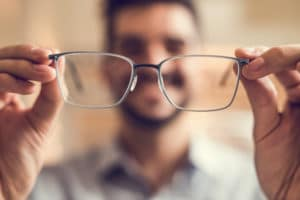 man holding up glasses with blurred background, vision test Springfield MA, eye exam Western MA, eye care Chicopee MA