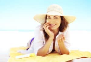 woman laying on the beach, summer eye care, sunlight eye protection, outdoor eye protection, eye exam Springfield MA