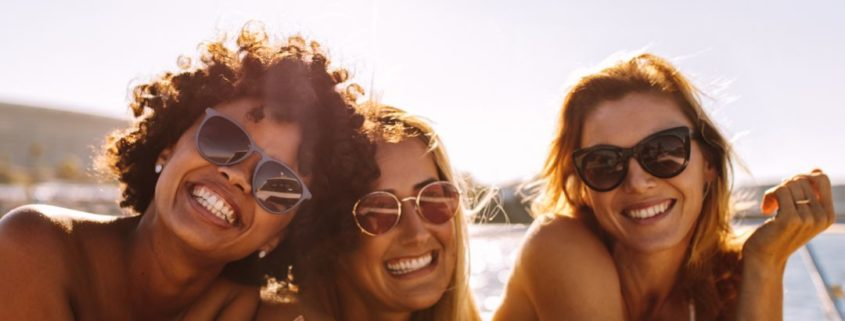 three women smiling and wearing sunglasses laying on a boat, eye protection, sun eye protection, eye care Springfield MA, eye care Western MA