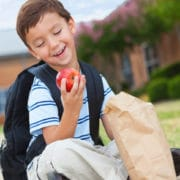 Little boy with backpack on holding an apple, snacks for eye health, eye care Springfield MA, eye doctor Western MA, Dr. John Papale