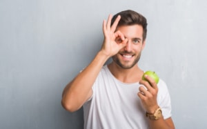 Man holding an apple making a circle with his hands around his eye, eye exam Springfield MA, comprehensive eye exam Western MA, eye doctor, Dr. John Papale